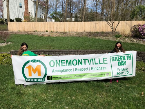 Addison and Elissa Schwartz hold the OneMontville Green In Day banner that was to be hung over Changebridge Road in Montville Township, NJ. The banner invites everyone to Wear Green May 15. Due to COVID-19, Green In Day 2020 will be held virtually.